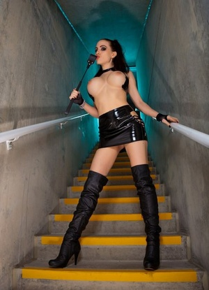 Sexy slut Katie Banks in glossy latex & hip high boots playing with her crop