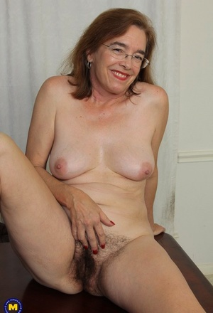 Mature American female pleasures her hairy thicket with a vibrator