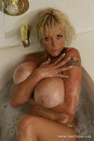 Mature blond soap up her huge breasts while taking a tub