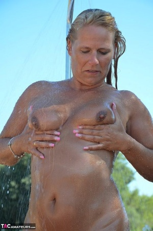 Mature blonde lubricates up her fit body before a dip in inground pool