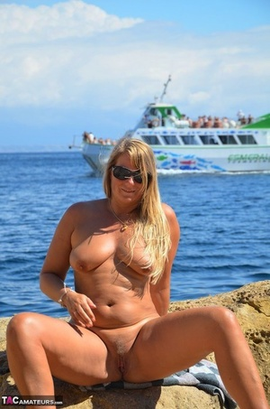 Amateur BBW with sagging boobs poses nude on rocks to delight of passing ships