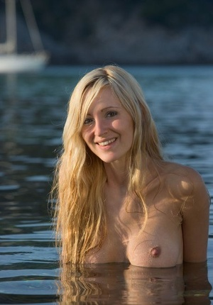 Young blonde girl Corinna stands fully naked in warm waters