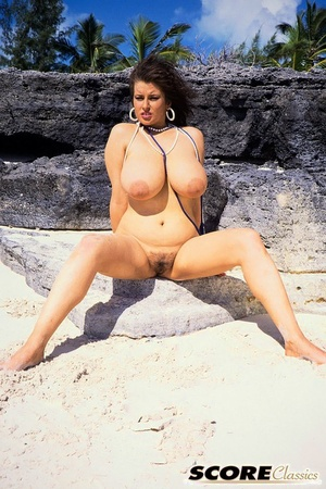 Super busty centerfold Lisa Phillips poses nude on a abandoned beach