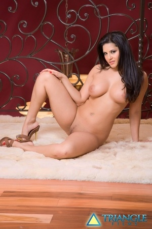 Busty ebony haired Sunny Leone lets her big knockers liberate & stretches long legs
