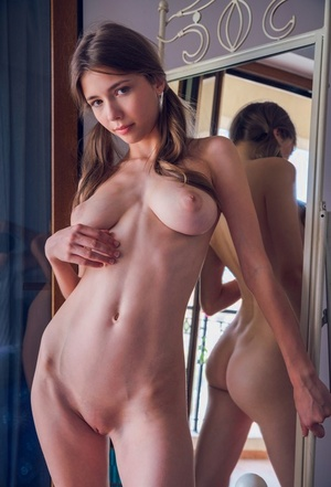 Slim young girl Mila Azul admires her reflection in mirror with no clothes on